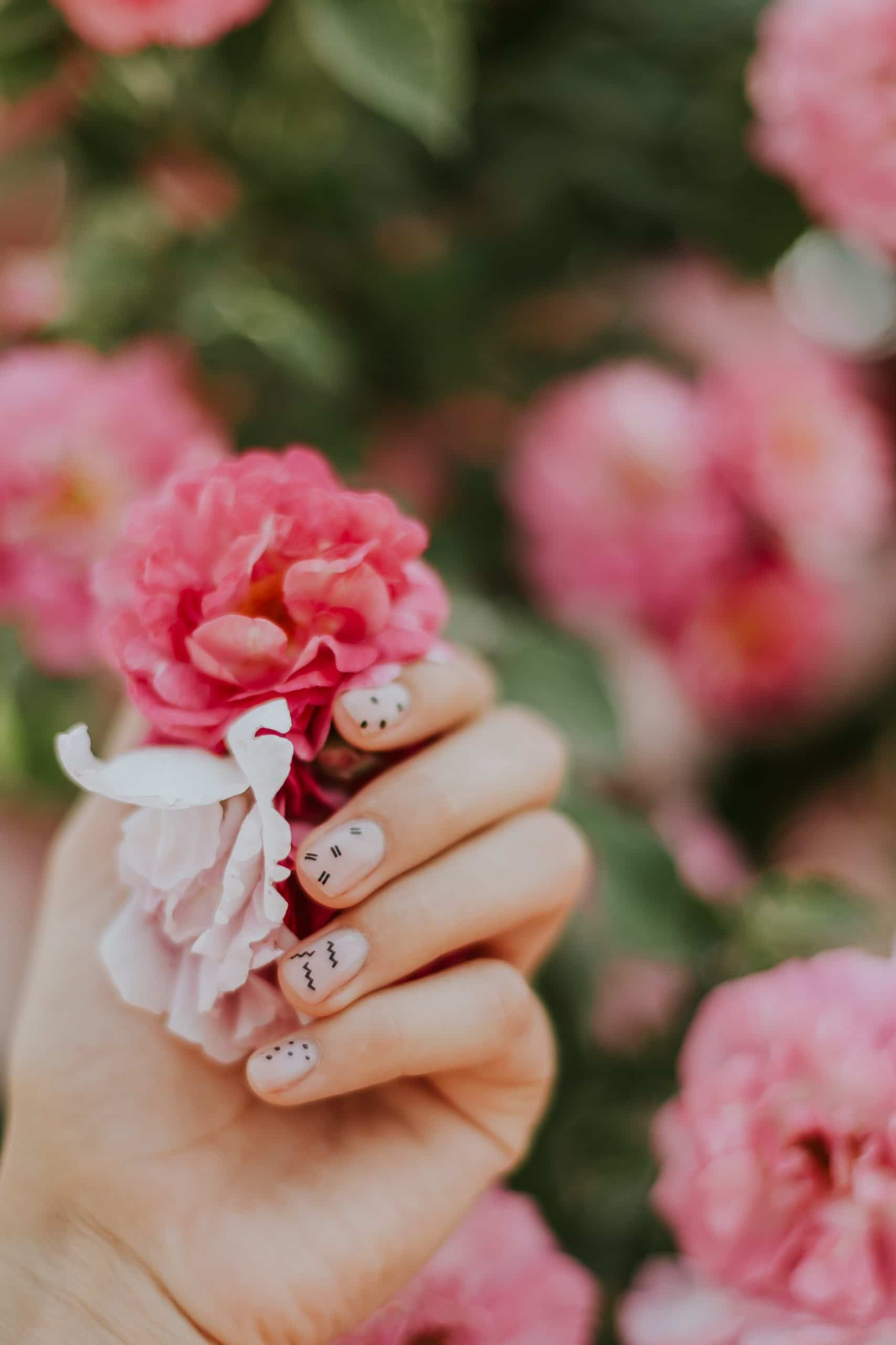 flower in hand with painted nails