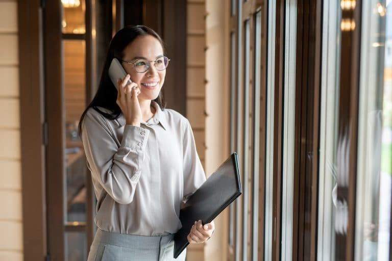 Happy young business agent with document and smartphone calling in restaurant