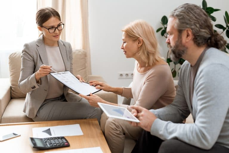 Young real estate agent pointing at document while consulting mature clients